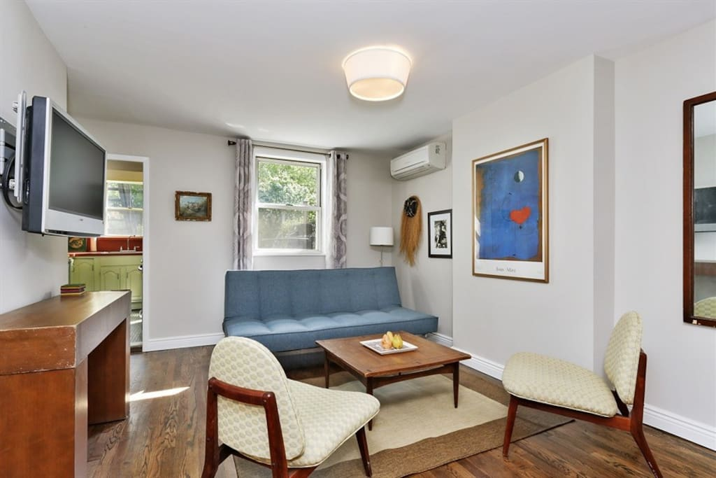 Living area features modern furnishings, fold down comfy sofa bed & cable TV.
