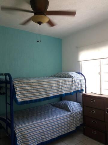 Recámara con litera, camas individuales, closet y ventiladores.