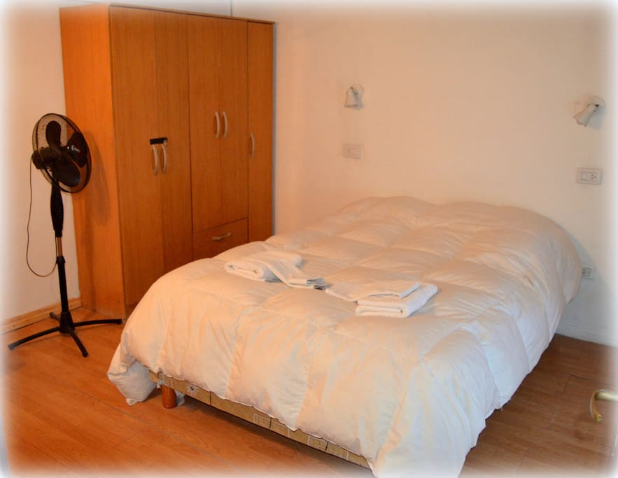 cuarto matrimonial amplio, toallas y toallones, ventilador y ropero.