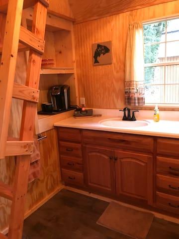 Kitchenette with kurig coffee machine and microwave and mini fridge.