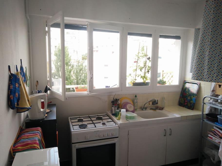Cuisine équipée et spacieuse avec fenêtre donnant sur le balcon