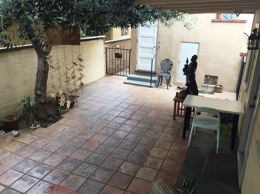 Terracotta courtyard under olive tree outside my door.