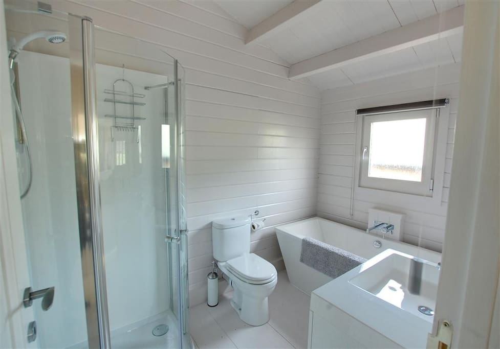 Bathroom with freestanding bath and shower unit.