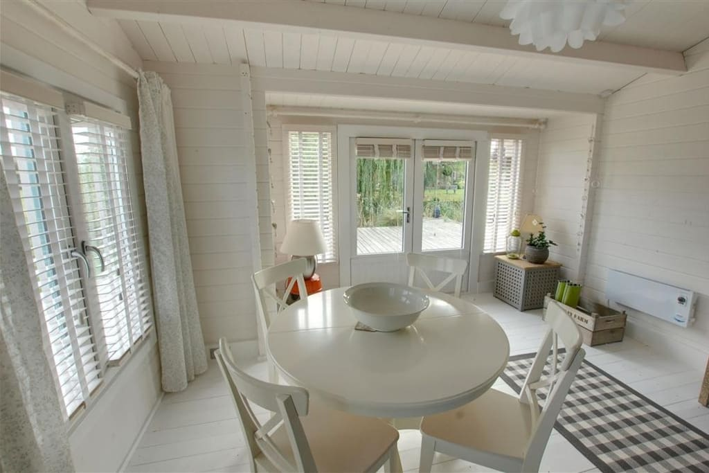 Open plan dining area overlooking decking and pond
