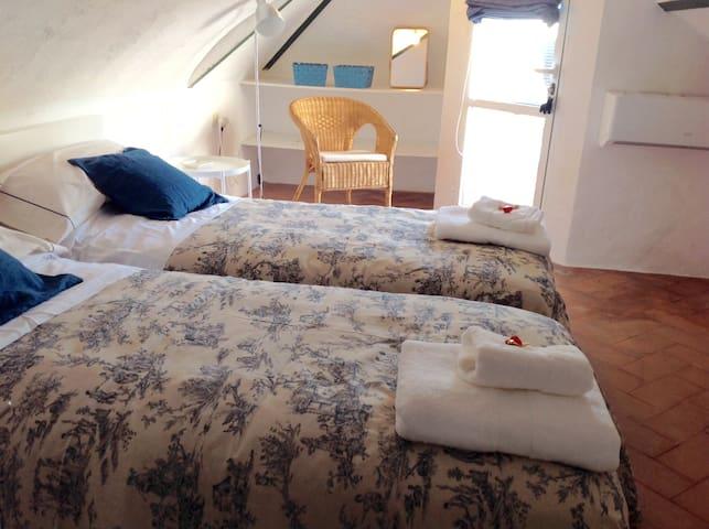 Cuarto de la buhardilla con sus dos camas y pequeña terraza.