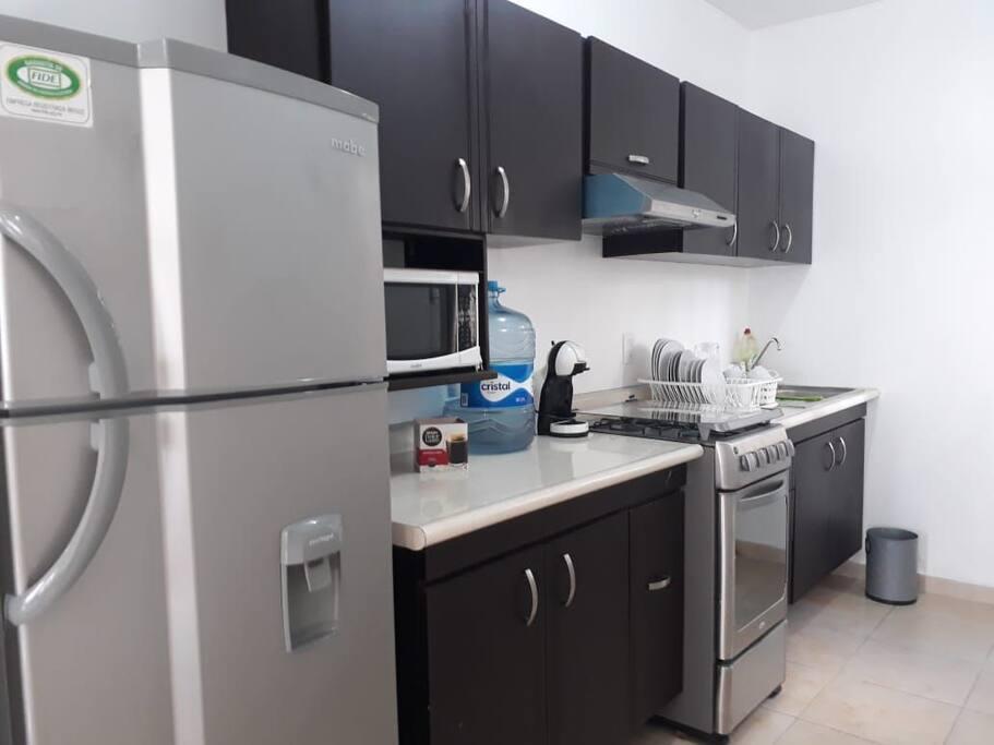 Contamos con una práctica cocina, al tamaño de tus necesidades. (Refrigerador, estufa, microondas)