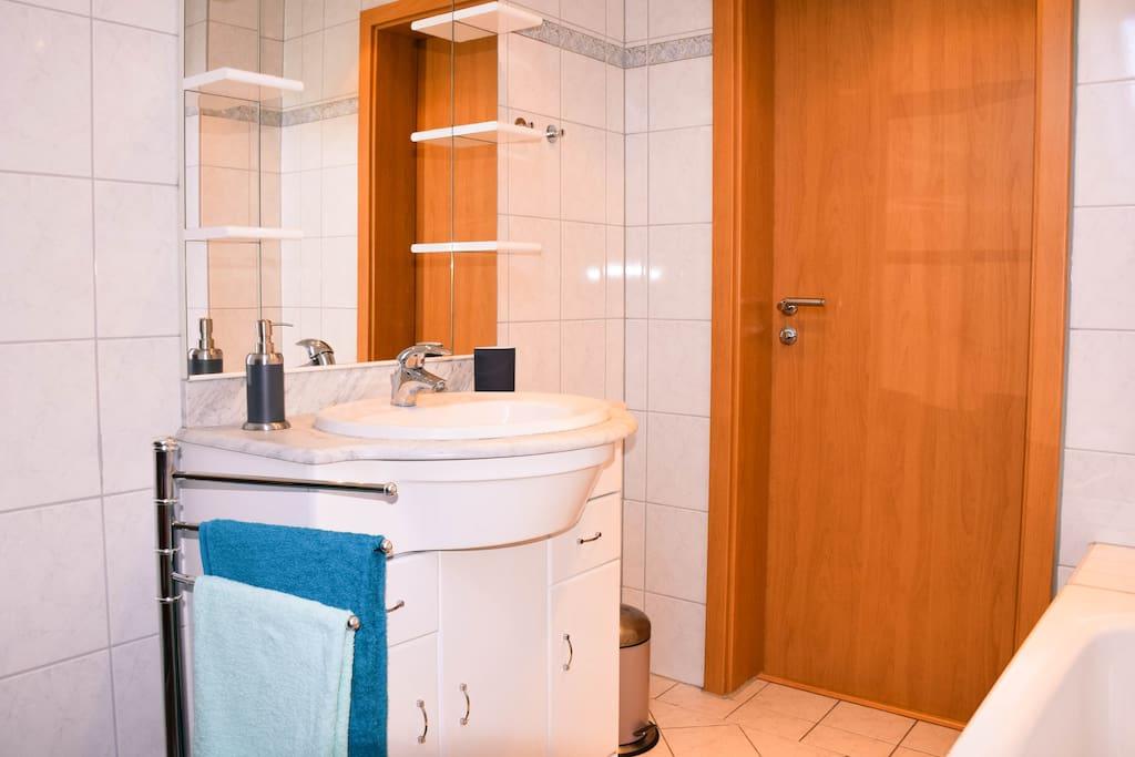 Ein großer Spiegel über dem Waschbecken lässt den Raum noch heller wirken