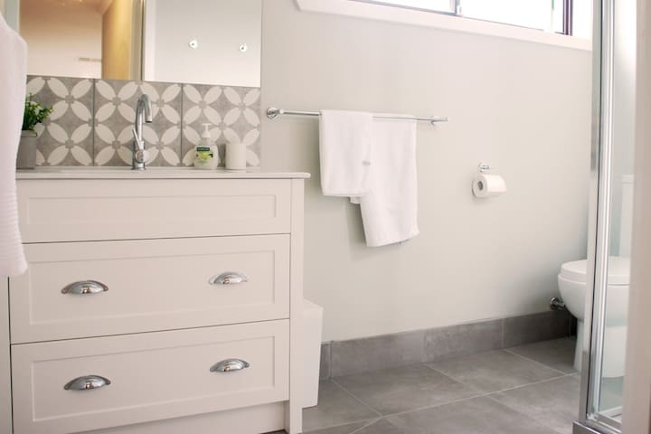 New main bathroom with vanity, toilet and large shower