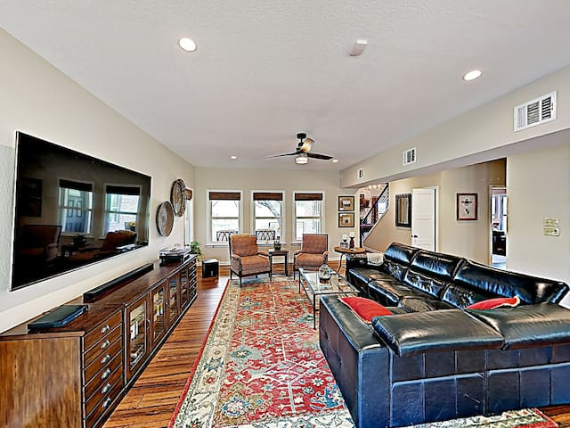 """The sunlit living area includes ample seating and an 83"""" smart TV."""