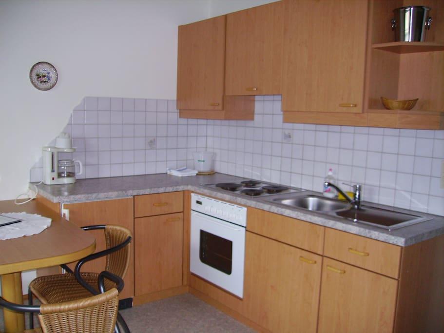 Küche mit Ausziehcouch und SAT-TV.