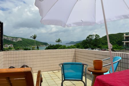 Experience a quiet, unique side of Hong Kong in a village house in Clear Water Bay. Sea 100m away, sea view roof, dbl bed, sofa bed, day bed, sitting room, rooftop, balcony, kitchen, 2 bathrooms and Wifi. Artistically decorated.  All you need
