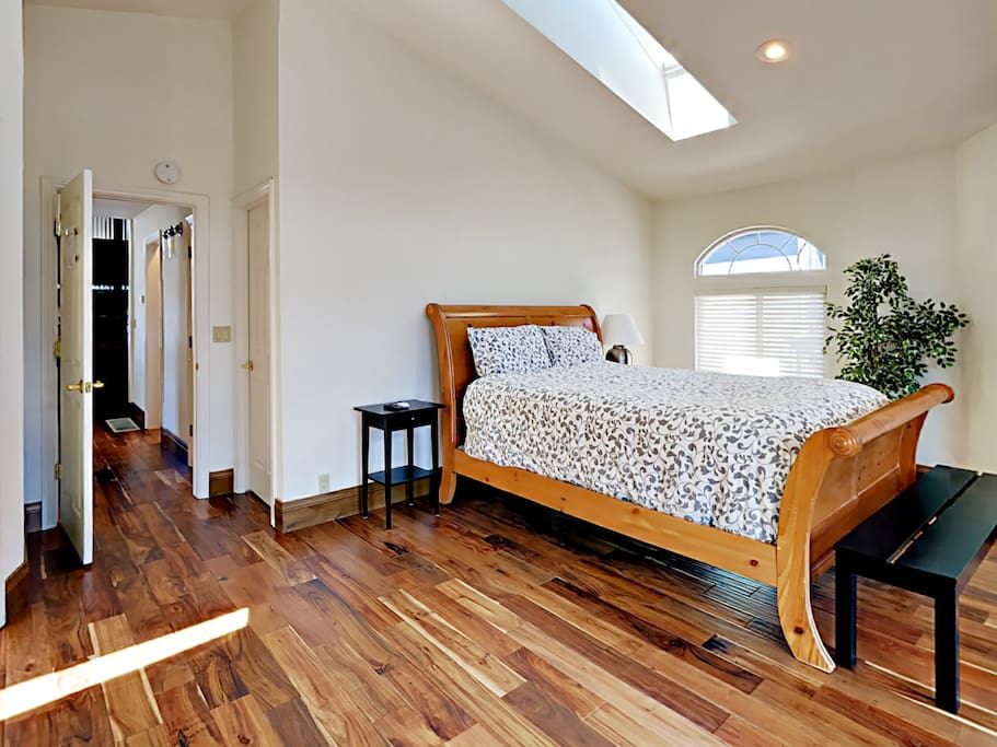 The bright master bedroom with queen-size bed
