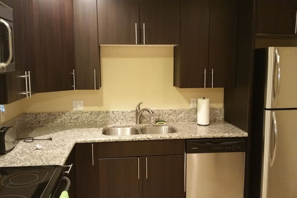 Kitchen with stainless steel sink and refrigerator and granite counter tops