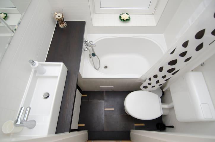 Small but well organized bathroom with a bath tub.