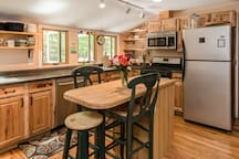 Full Kitchen with butcher block island.  Kitchen sink windows look out onto large deck.
