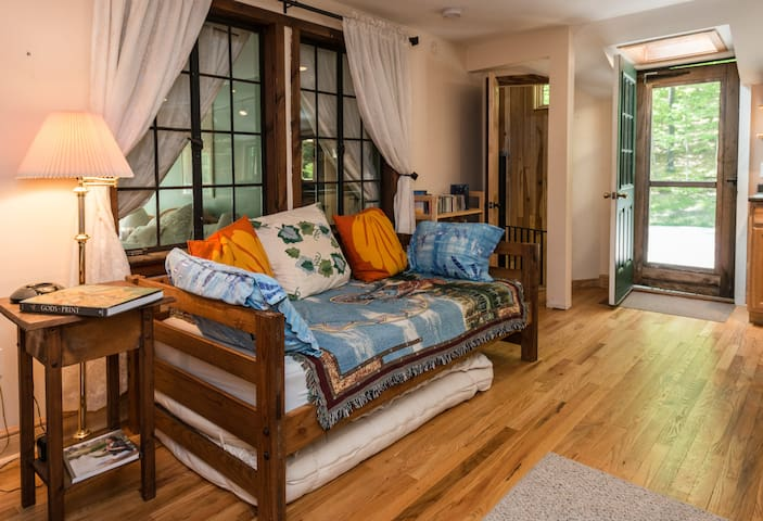 Main Room has single bed that doubles as a couch, a large desk, futon and kitchen island. Screen door leads out to large deck private entrance.