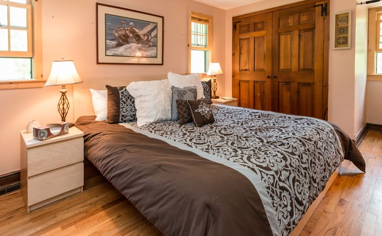 King sized bed in separate bedroom with stall shower in bathroom.