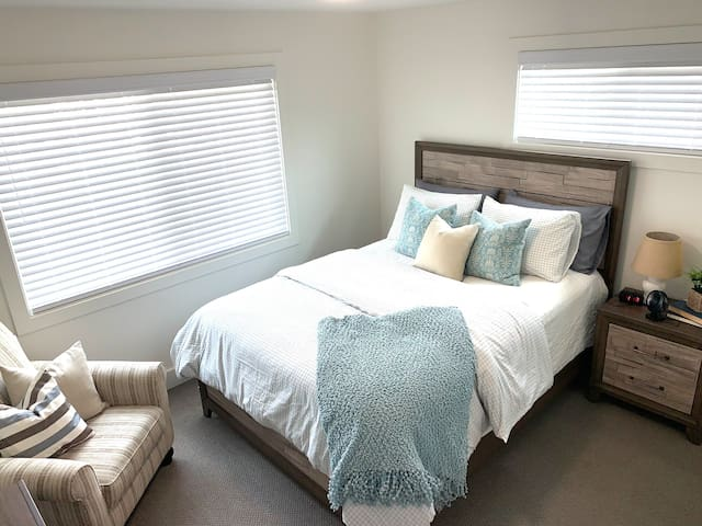 Master Bedroom, high quality mattress, extra pillows, fan, alarm clock, tv, phone charging area, and reading chair.