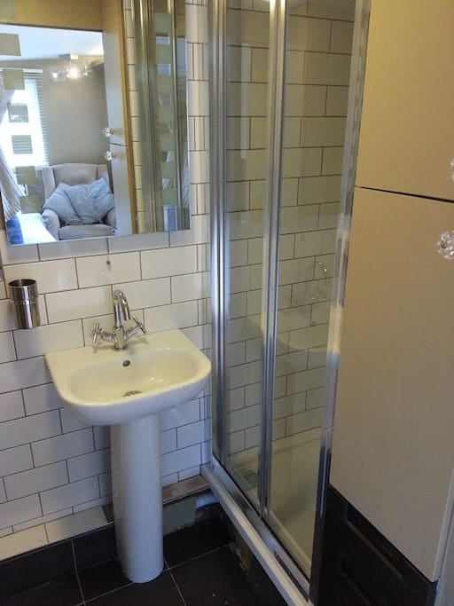 Adjoining bathroom with sliding door, electric shower and w/c.