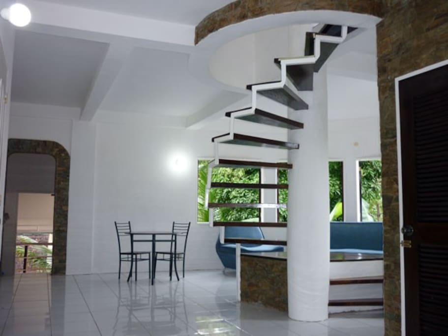 The view from the entrance foyer past the spiral staircase leading up to the private master area. In the background is the living room and to the left the back entrance leading to laundry and service kitchen