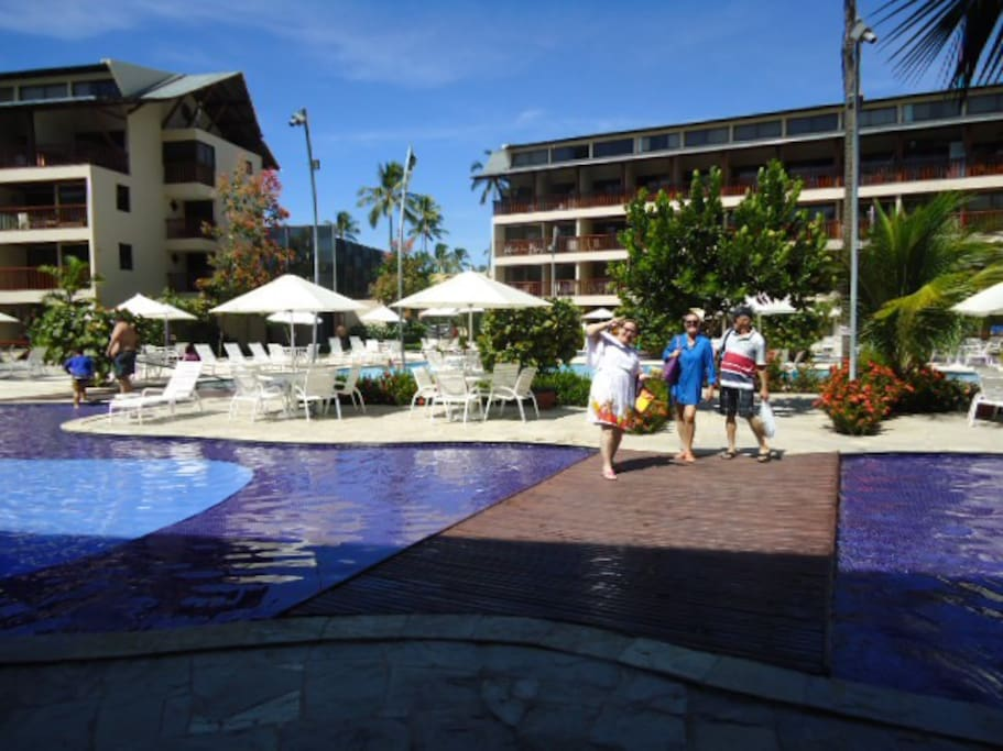 Vista familia desfrutando area interna das piscinas.