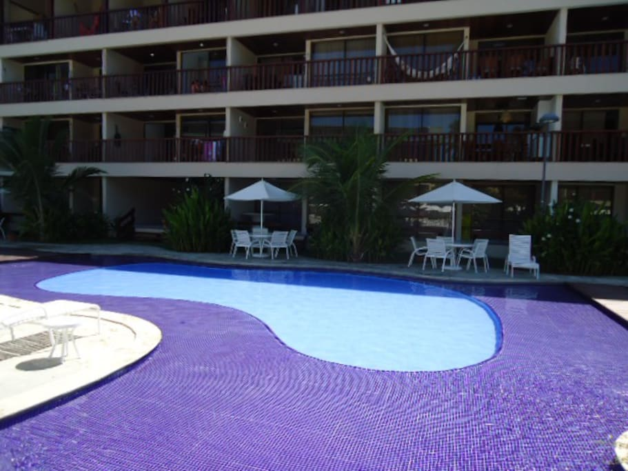 Vista frontal do flat com piscinas ao ar livre.