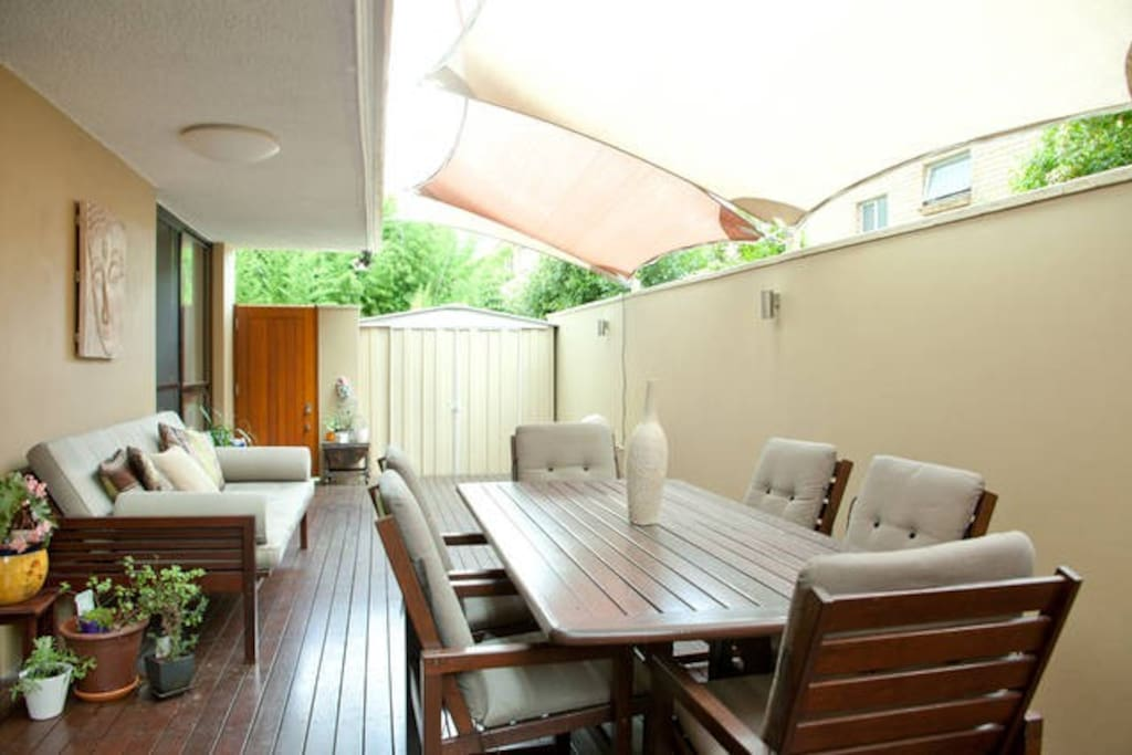 North facing deck with outdoor seating and daybed plus sails for shade, fairy lights at night and fountain