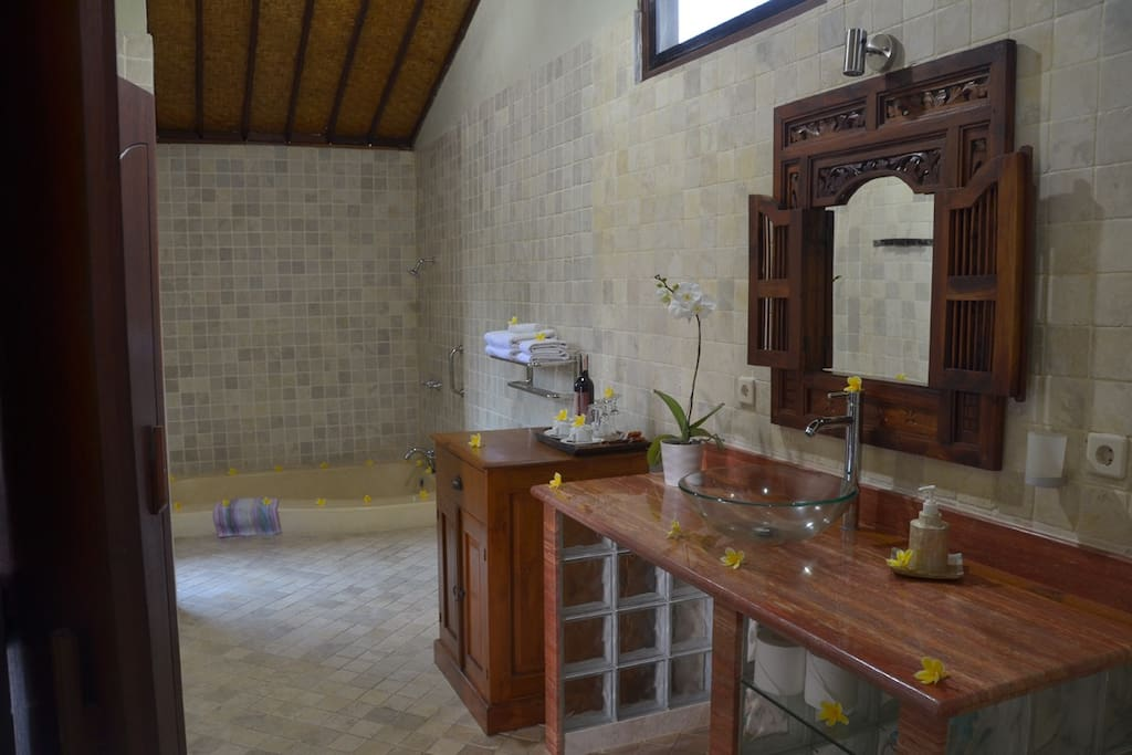 Spacious bath room with marble vanity, marble floor and walls and oversized terrazzo bath tub.