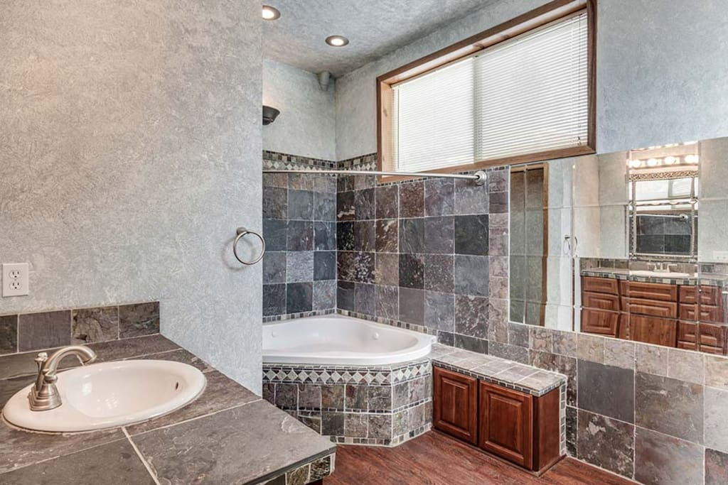 This large bathroom looks larger yet, with all the mirrors. The photos  really don't do it justice.  Come and see. The jetted tub also has a large shower.