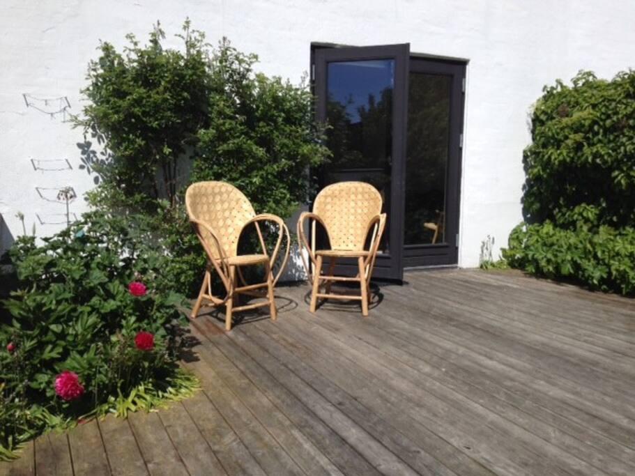 Solrig terrasse med udsigt til havens ro og frugttræer.