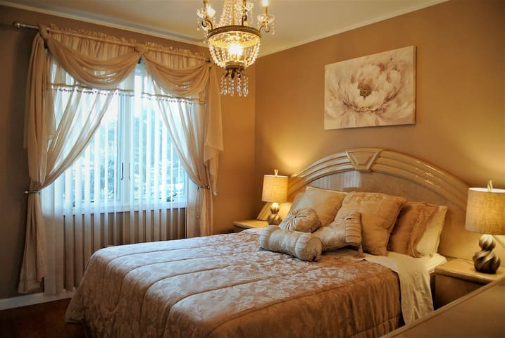 Beautifully decorated french-style queen size bedroom with a large window.