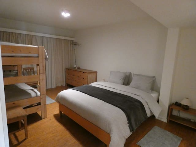 Slaapkamer met dubbel bed en stapelbed met deur naar smal terras. En toegang tot grote badkamer met ligbad.