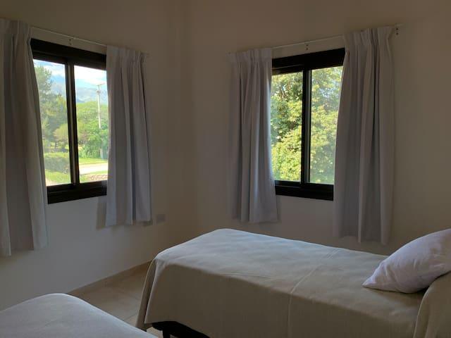 Dormitorio con dos sommier y ventanas con vistas a la montaña.