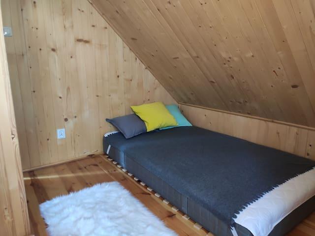 Pokój na górze z biurkiem komodą i nowym materacem do spania