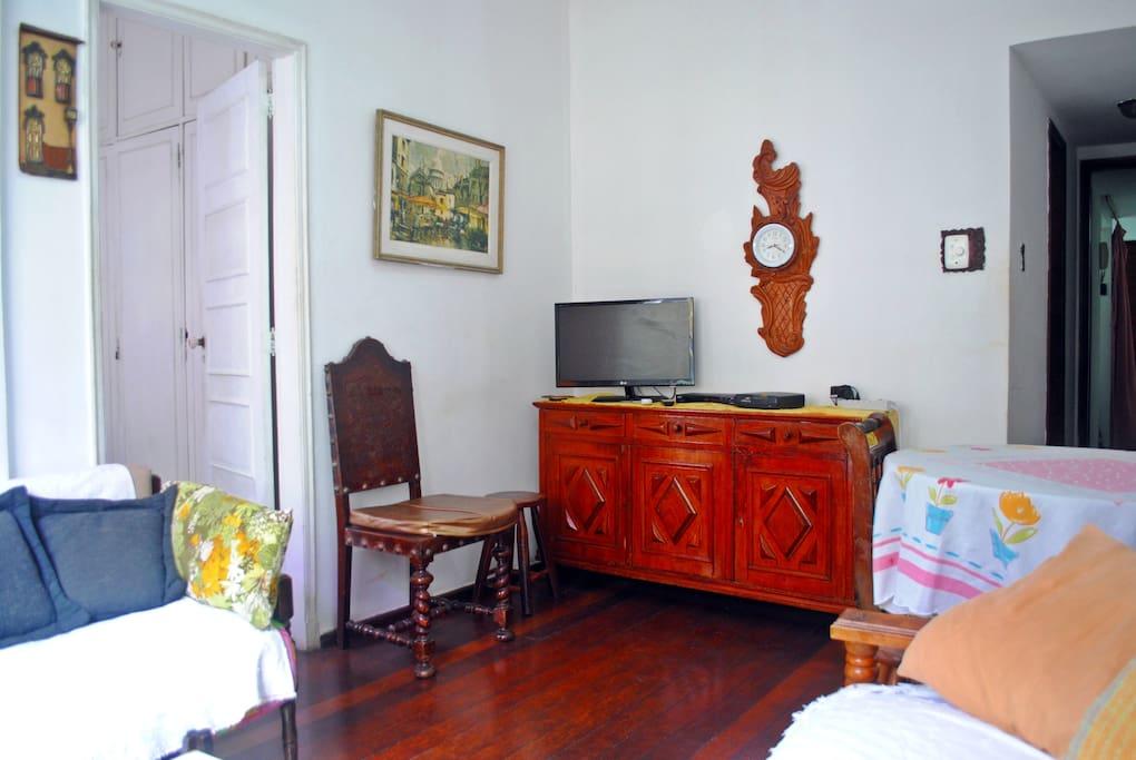 Sala de TV com sofá cama e mesa de jantar