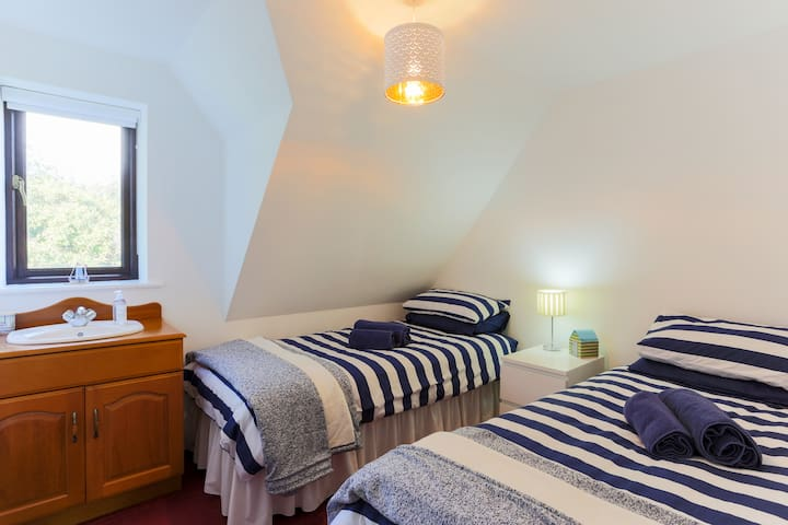 First floor Bedroom No. 4 with 2 single beds and views over the  back walled garden.  Sleeps 2