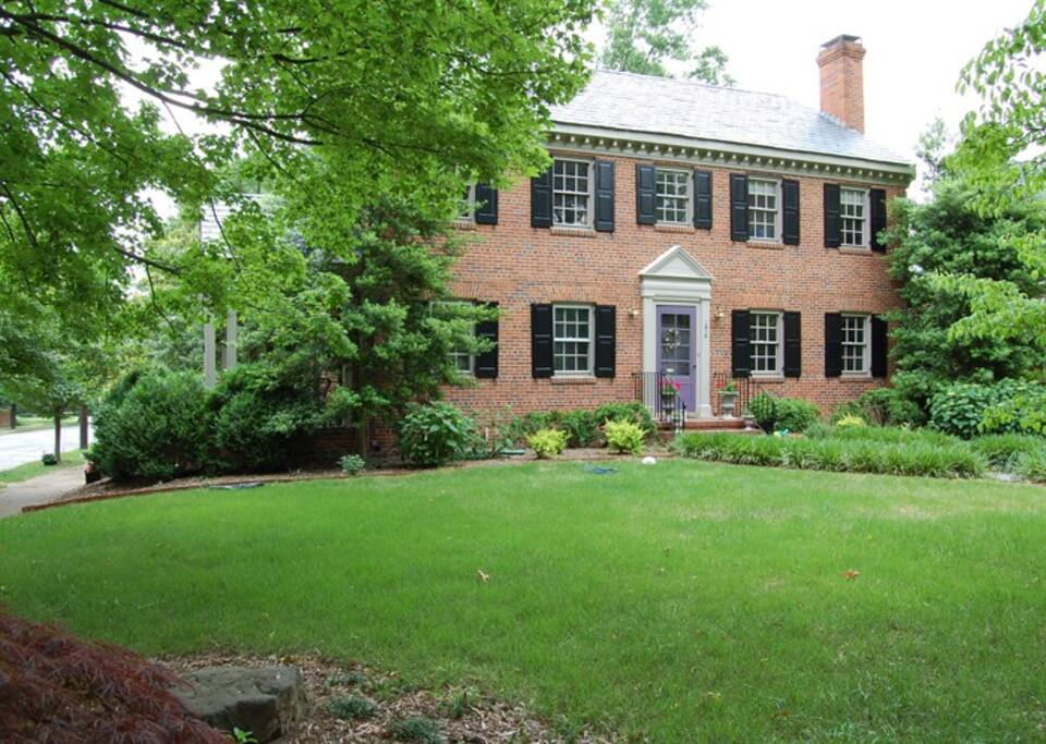 Two story brick colonial sits on a city corner lot