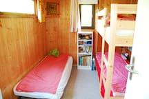 Kinderzimmer mit Gästeliege, Kinderbüchern, Spielzeug und Kleiderschrank.