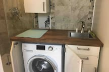 Sink, cabinets and washer/dryer.
