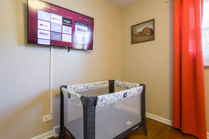 Bedroom #2. Queen size bed and Graco Pack 'n Play Portable Playard. The TV is a ROKU TV and has complimentary Youtube TV ready for you to enjoy.   Hangers and Luggage Racks are in each bedroom closet.