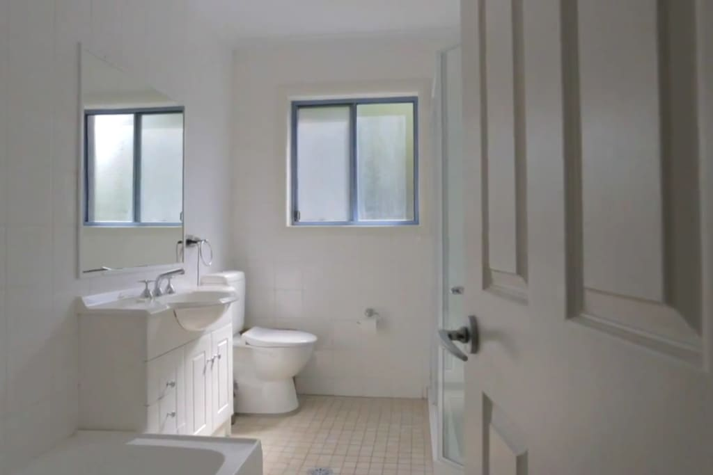 very clean bathroom with bathtub, shower and opposite to available  room.