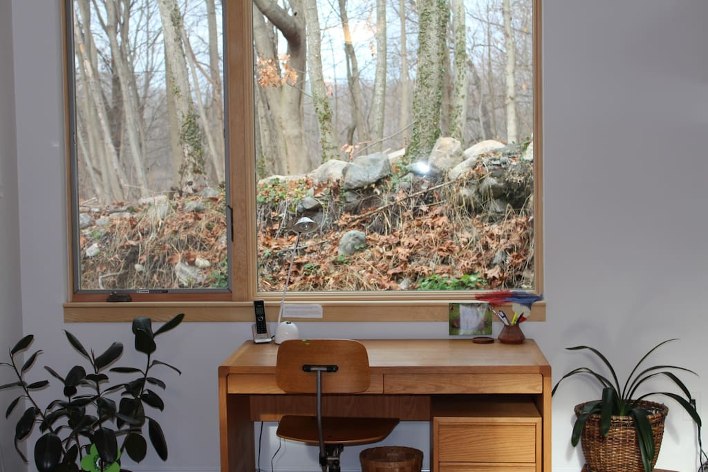 Desk for writing, reflecting looks out to old stone wall and conservation land.
