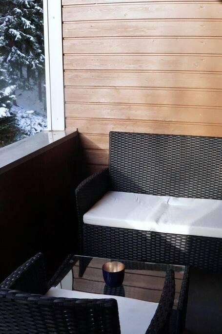 Auf der großzügigen Loggia haben bis zu vier Personen Platz. Die gemütliche Lounge-Ecke lädt zum Verweilen ein: Im Winter bei Glühwein, im Sommer bei einem Prosecco.