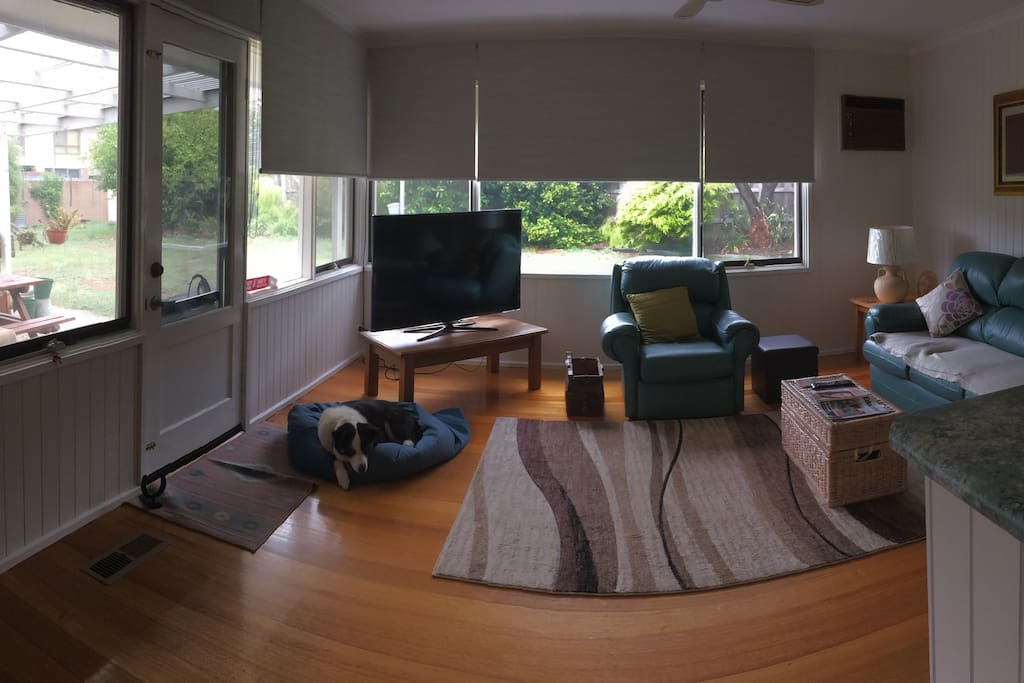 Living room with television and access to undercover pergola and barbeque.