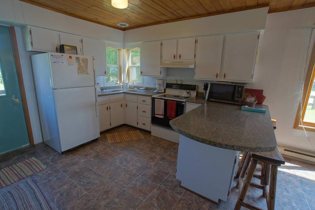 Fully equipped kitchen complete with stove, refrigerator, microwave, toaster, and coffee maker