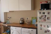 Kitchen with washingmachine, dryer and fridge.