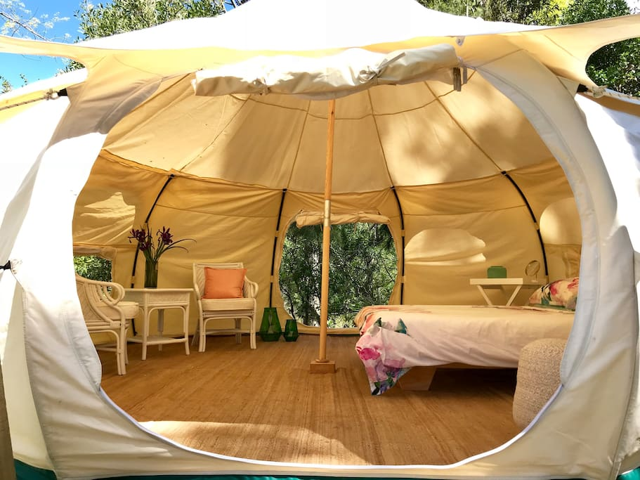 Glamping tent interior with queen sized bed, chairs, bedside tables and hanging space.