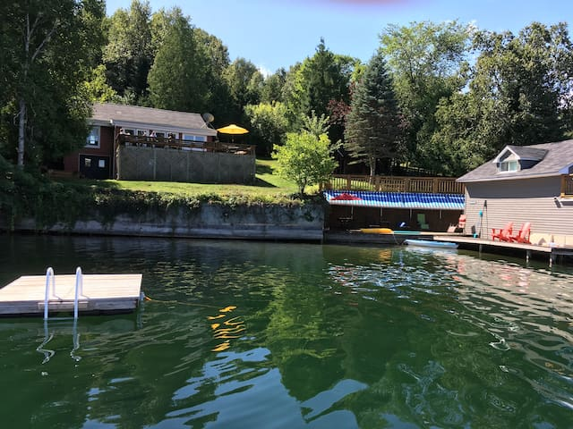 beautiful water front with expansive decks,  raft , boathouse and cottage