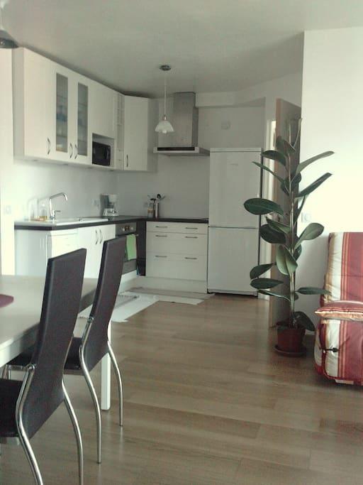 Conviviale, la salle à manger, avec sa grande table pour 4 convives, la cuisine ouverte et le salon