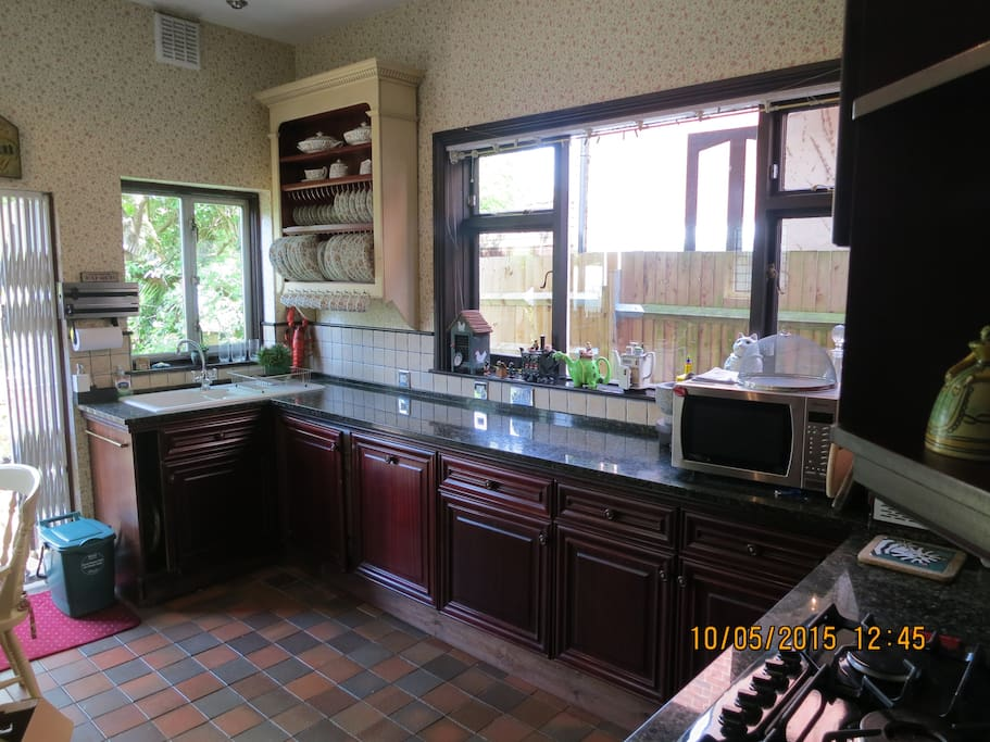 Spacious country-style kitchen with mahogany woodwork and granite surfaces, plus seating area for dining
